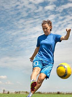 Eine junge Frau im Sportdress spielt Fußball.