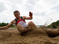Ein Weitspringer landet im Sand.