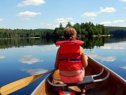 Ein junges Mädchen rudert in einem Kanu auf einem See.