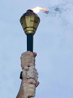 Drei Hände halten gemeinsam eine brennende Fackel.
